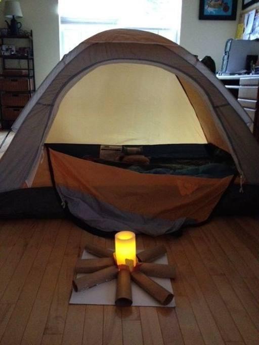 Il campeggio in salotto è un grande classico. Da copiare la realizzazione del fuoco: i tubi di cartone dei rotoli di carta diventano ciocchi di legno, una candela fa le veci delle fiamme