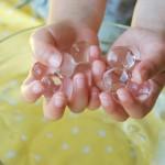 Le biglie magiche. Serve un sacchetto di palline di gomma, una coppa e dell'acqua. Si immergono le piccole sfere in acqua e si lasciano ammollo per 4-6 ore. L'effetto è strabiliante: le biglie si espandono e diventano invisibili